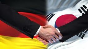 Poignée de main de l'Allemagne et de la Corée du Sud, amitié internationale, fond de drapeau banque de vidéos