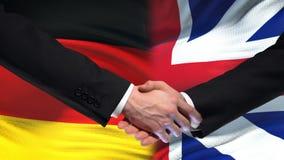 Poignée de main de l'Allemagne et de la Grande-Bretagne, amitié internationale, fond de drapeau banque de vidéos