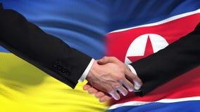 Poignée de main de l'Ukraine et de la Corée du Nord, amitié internationale, fond de drapeau banque de vidéos