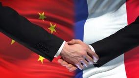 Poignée de main de la Chine et de Frances, relations internationales d'amitié, fond de drapeau banque de vidéos