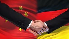 Poignée de main de la Chine et de l'Allemagne, relations internationales d'amitié, fond de drapeau clips vidéos