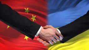 Poignée de main de la Chine et de l'Ukraine, relations internationales d'amitié, fond de drapeau banque de vidéos