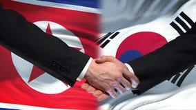 Poignée de main de la Corée du Nord et de la Corée du Sud, amitié internationale, fond de drapeau banque de vidéos