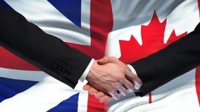 Poignée de main de la Grande-Bretagne et du Canada, amitié internationale, fond de drapeau banque de vidéos