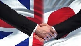 Poignée de main de la Grande-Bretagne et du Japon, amitié internationale, fond de drapeau clips vidéos