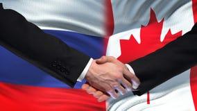 Poignée de main de la Russie et de Canada, sommet international d'amitié, fond de drapeau banque de vidéos