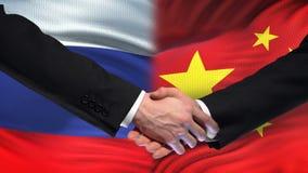 Poignée de main de la Russie et de la Chine, sommet international d'amitié, fond de drapeau banque de vidéos