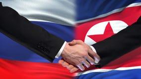 Poignée de main de la Russie et de la Corée du Nord, amitié internationale, fond de drapeau banque de vidéos