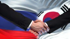 Poignée de main de la Russie et de la Corée du Sud, amitié internationale, fond de drapeau banque de vidéos