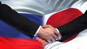 Poignée de main de la Russie et du Japon, sommet international d'amitié, fond de drapeau clips vidéos