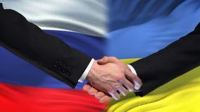 Poignée de main de la Russie et de l'Ukraine, sommet international d'amitié, fond de drapeau banque de vidéos