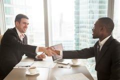 Poignée de main multiraciale de deux hommes d'affaires au-dessus de bureau après e Image libre de droits