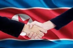 Poignée de main de négociation avec le drapeau de la Corée du Nord Images stock
