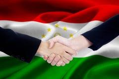 Poignée de main de réunion avec le drapeau du Tadjikistan Photographie stock
