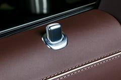 Poignée de porte avec des boutons de contrôle de serrure d'une voiture de tourisme de luxe Intérieur en cuir rouge de la voiture  Photo stock