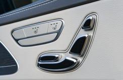 Poignée de porte avec des boutons de contrôle de siège de puissance d'une voiture de tourisme de luxe Intérieur de cuir blanc de  Photos libres de droits