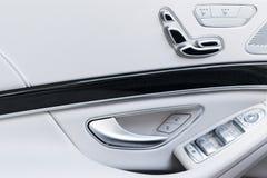 Poignée de porte avec des boutons de contrôle de siège de puissance d'une voiture de tourisme de luxe Intérieur de cuir blanc de  Photo stock