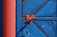 Poignée de porte avec l'ornement de forme de coeur en rouge sur le fond bleu Photo libre de droits