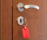 Poignée de porte avec la clé insérée dans le trou de la serrure avec le keyholder rouge Photographie stock libre de droits