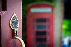 Poignée de porte décorative avec la cabine de téléphone anglaise à l'arrière-plan Photographie stock