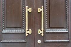 Poignée de porte en métal de plan rapproché sur la porte d'entrée en bois images libres de droits