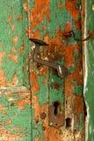 Poignée de porte et verrou rouillés sur la vieille porte verte superficielle par les agents photographie stock