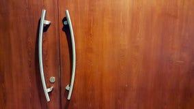 Poignée de porte moderne de style sur la porte en bois naturelle images stock