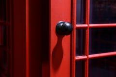 Poignée de porte noire sur la cabine de téléphone anglaise images libres de droits