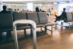 Poignée de valise avec le fond d'aéroport de tache floue Photo libre de droits