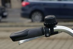 Poignée en caoutchouc noire aux commandes du vélo et de la cloche Plan rapproché images stock