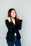 Poignée et sourire asiatiques d'exposition de dame de portrait sur l'isolat gris Images libres de droits