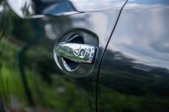 Poignée haute étroite sur la portière de voiture noire photographie stock libre de droits