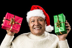 Poignant Aged Man Showing Red And Green Xmas Gifts. Honorable old man with Santa Claus cap his showing a red and a green wrapped present. Emphatic gaze, coy Stock Photography
