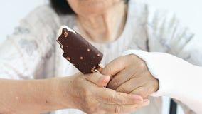 Poignet cassé par femme agée appréciant la crème glacée  clips vidéos