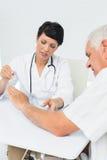 Poignet de examen de patients de physiothérapeute avec le goniomètre Photographie stock libre de droits