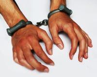 Poignets et mains dans des menottes photographie stock libre de droits