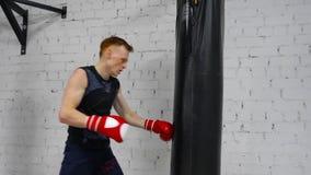 Poinçons s'exerçants d'homme de boxeur par le sac de combat dans le club de combat Homme professionnel de boxeur dans les gants e banque de vidéos