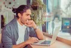 Poing acéré d'homme nerveux tout en observant des nouvelles sur l'ordinateur portable image libre de droits
