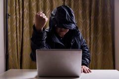 Poing asiatique d'exposition de pirate informatique tout en entaillant le réseau informatique Photos stock