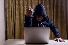 Poing asiatique d'exposition de pirate informatique tout en entaillant le réseau informatique Photographie stock libre de droits