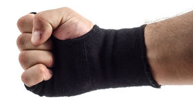 Poing de boxeur avec des enveloppes de poignet sur un fond blanc Images stock