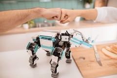 Poing de salutation dans un plan rapproché de poing Le type et la fille dans la cuisine Est tout près un robot Images stock