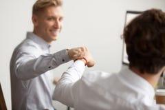 Poing masculin de sourire de collègues se cognant, concept de soutien de travail d'équipe, Photo libre de droits