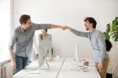 Poing masculin gai de collègues se cognant célébrant le thé réussi Image stock