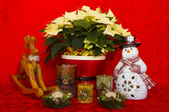 Poinsettia in einem roten Korb mit Kerzen, Schneemann und Ren Lizenzfreie Stockbilder