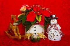 Poinsettia in einem weißen Korb mit Kerzen, Schneemann und Ren Stockfotografie