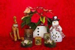 Poinsettia in einem weißen Korb mit Kerzen, Schneemann und Ren Lizenzfreie Stockfotografie