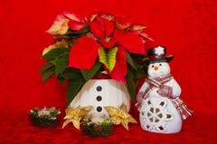 Poinsettia in einem weißen Korb mit Kerzen und Schneemann Stockbild