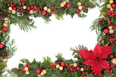 Poinsettia Floral Border. Christmas floral background border with red poinsettia flower, baubles, holly, mistletoe and winter greenery over white stock photo