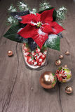 Poinsettia, golden baubles, Chrustmas tree on wooden table Stock Photos